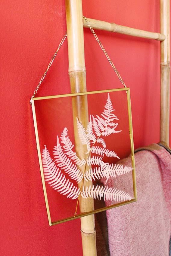lijst met droogbloemen goud en wit hangend aan ladder