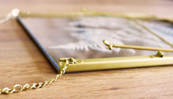 lijst met droogbloemen goud liggend op tafel